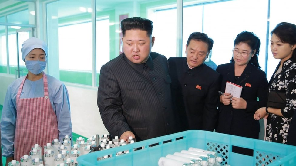 Kim Jong Un holds clear liquid samples in bottles at factory visit