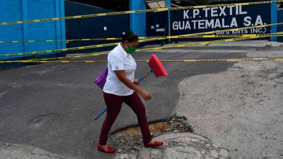 Mujer con elementos de limpieza camina en Guatemala