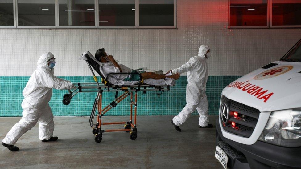 Profissionais de saúde carregando homem em maca com suspeita de covid