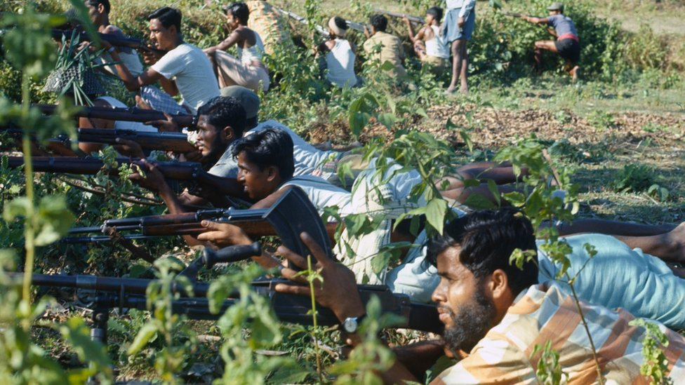 Many Bangladeshi men lined up next to each other, lying on the ground holding rifles