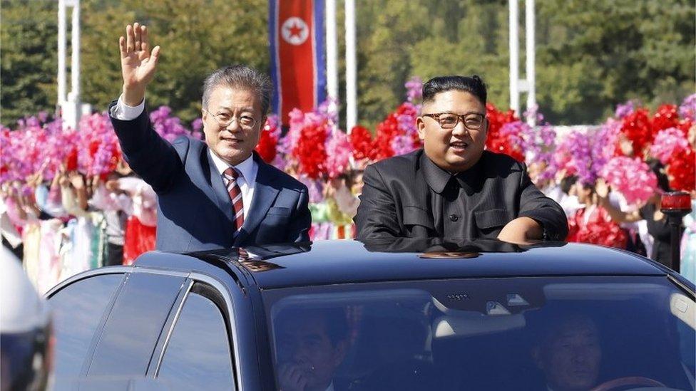 Moon Jae-in (izquierda) y Kim Jong-un saludan.