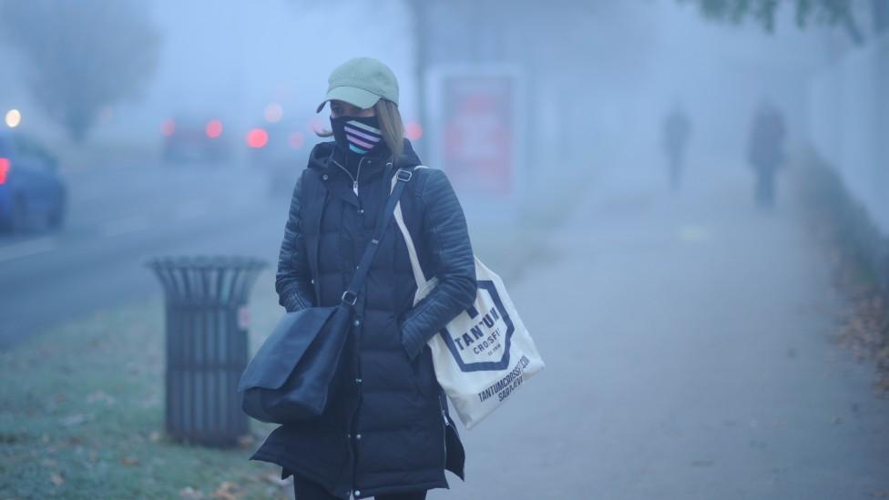 Mujer caminando en una calle contaminada en Sarajevo
