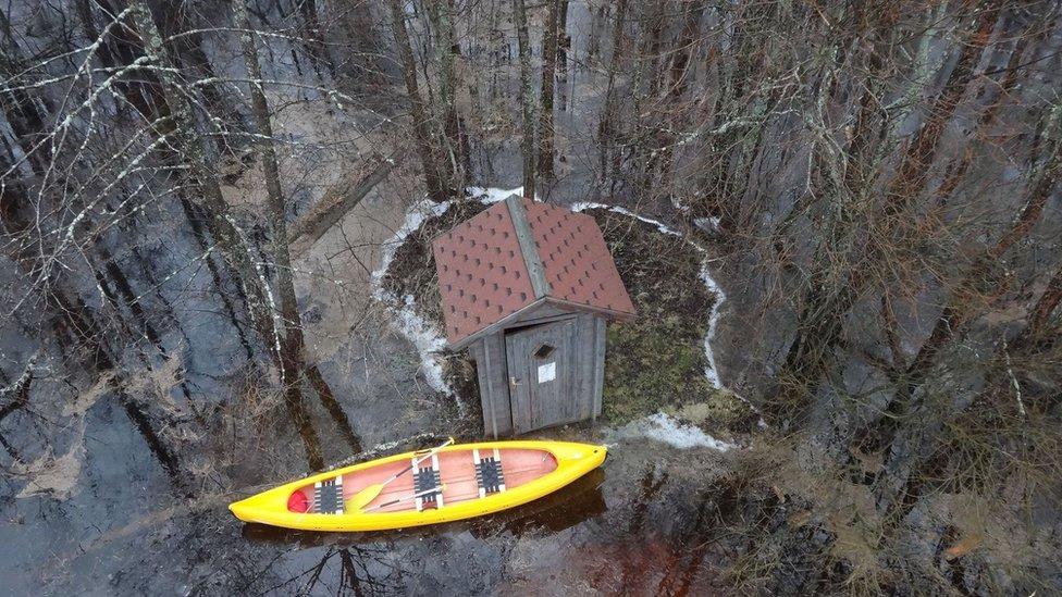 Una casita y una canoa en medio de un bosque vistas desde el aire