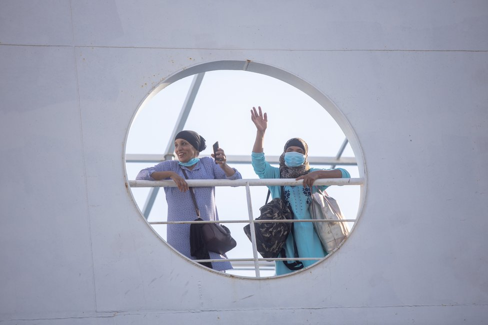 Two masked women wave from the deck of a boat.