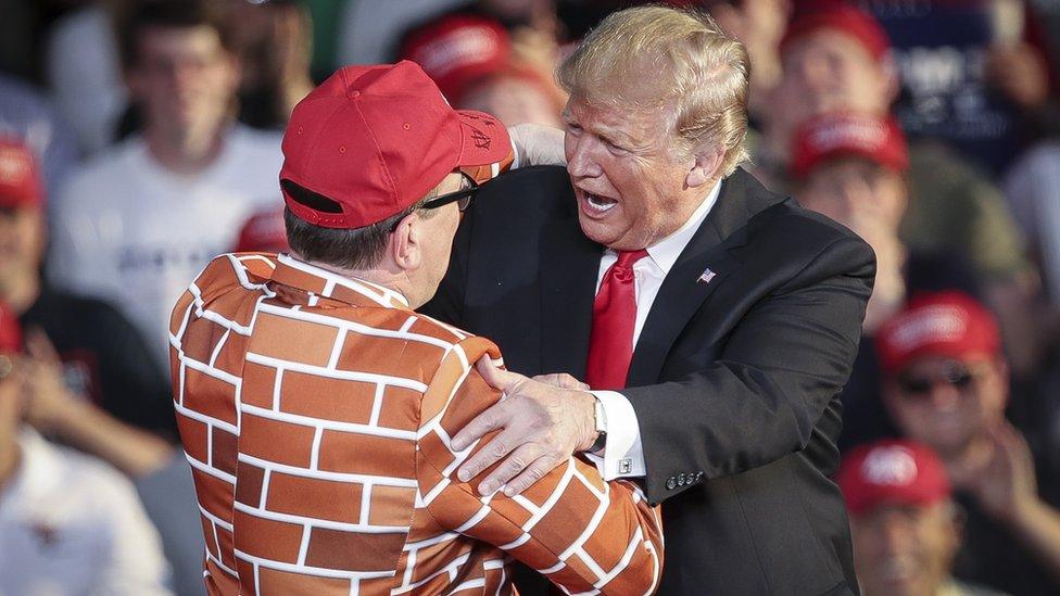 Trump saluda a un seguidor vestido con un traje de muro.