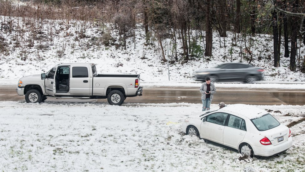A motorist checks his phone after sliding off the road in the snow on December 9, 2018 in Charlotte, North Carolina