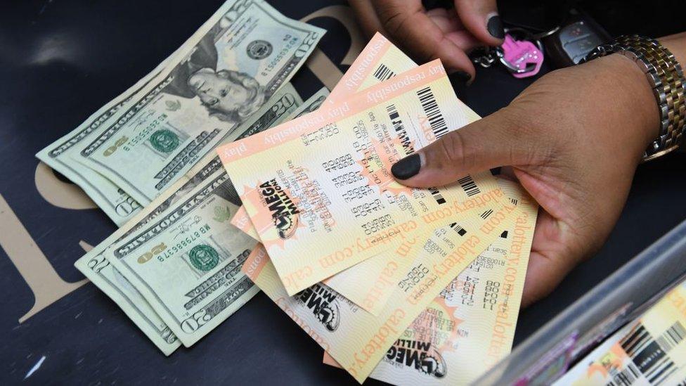 Manos de una mujer con dólares y boletos de lotería.