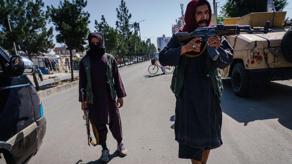 Un talibán apunta a los manifestantes.