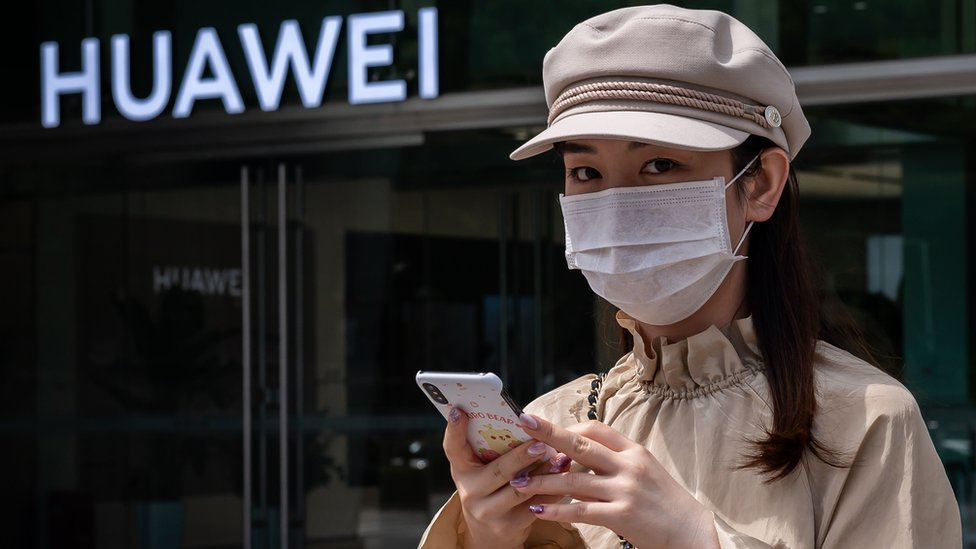 Una mujer con un teléfono en la mano.