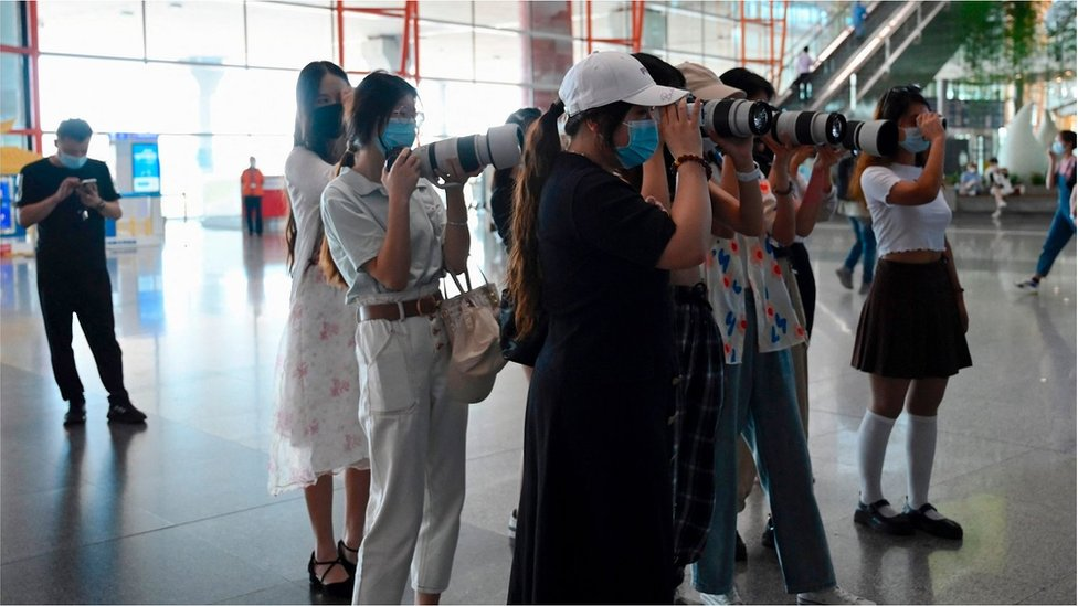 Fans holding cameras wait for celebrities at Beijings Capital Airport in Beijing on August 25, 2021.