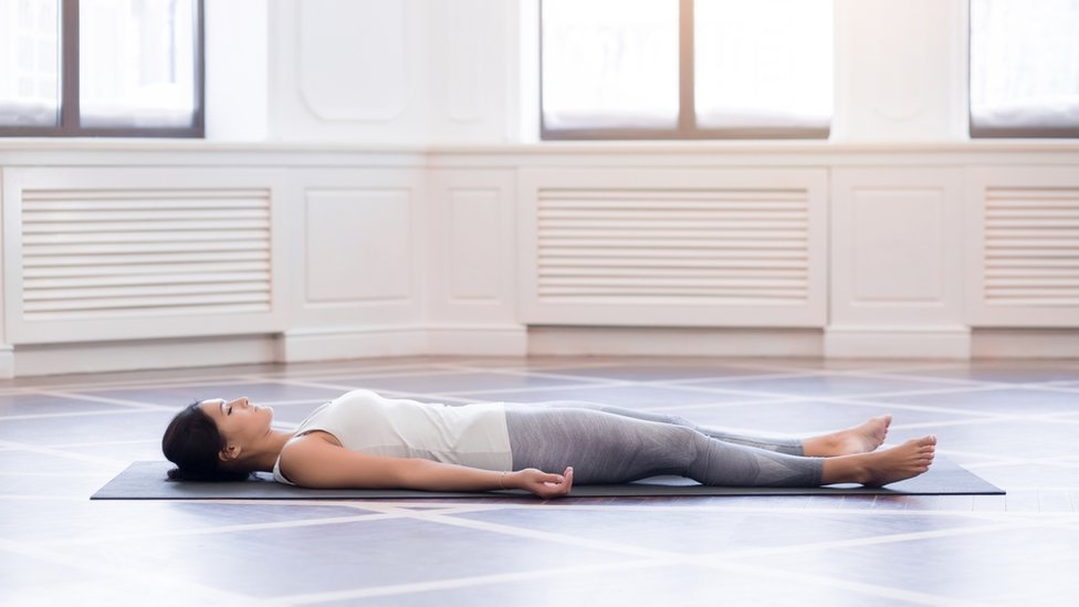 A woman relaxing on a floormat in an empty room