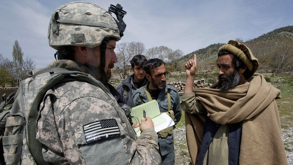عناصر المخابرات العسكرية الأمريكية يتحدثون إلى ممثل حكومة المقاطعة خلال دورية إعادة الاستطلاع في قرية مير كييل، في شرق أفغانستان في 7 مايو/أيار 2009