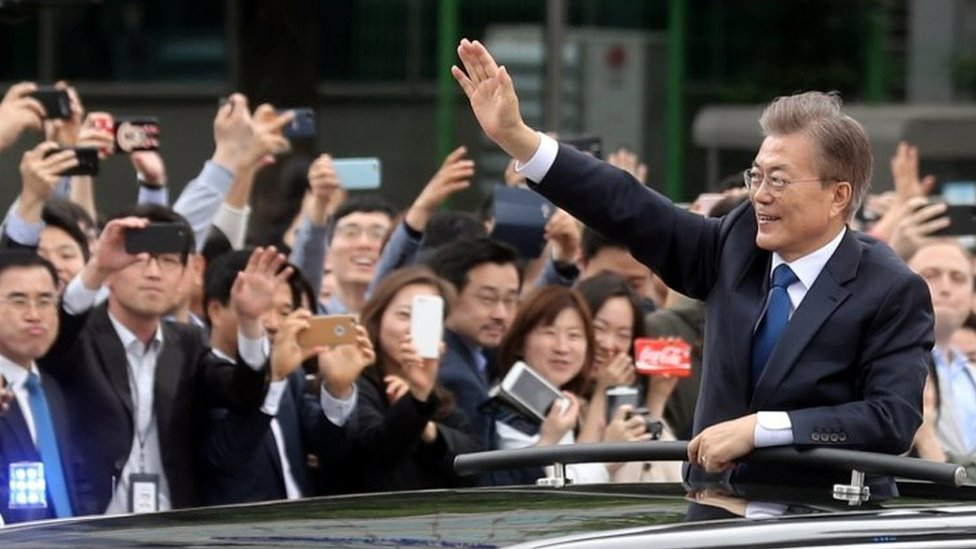 South Korean President Moon Jae-in (right) waves from a car as he heads to the presidential Blue House in Seoul. Photo: 10 May 2017