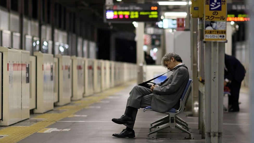 A businessman sleeping on a bench at a Tokyo train station