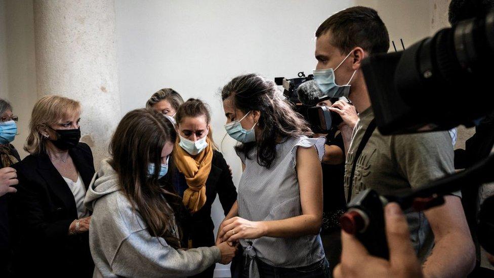 La acusada Valérie Bacot (centro) llega acompañada por su familia y rodeada de periodistas al Palacio de Justicia de Chalon-sur-Saone, en el centro oeste de Francia.