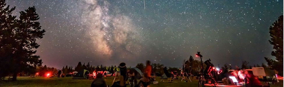 A group of people stargazing, the sky is lit with meteorites and the milky way