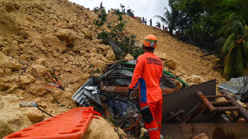 Rescue workers digging into rubble at the site of the landslide