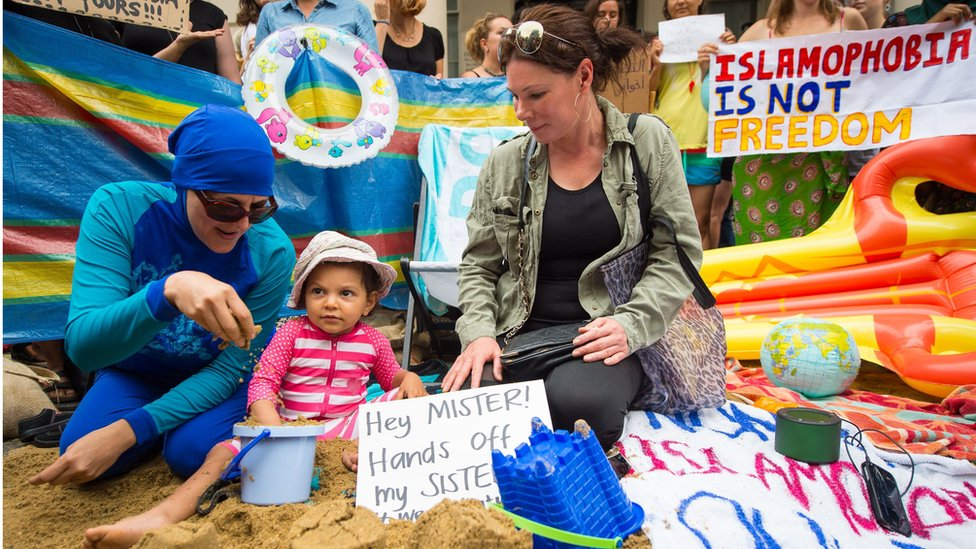 Two women, one wearing a burkini and one not, sit next to a child playing in the sand; a sign reads 'hey mister hands off my sister'