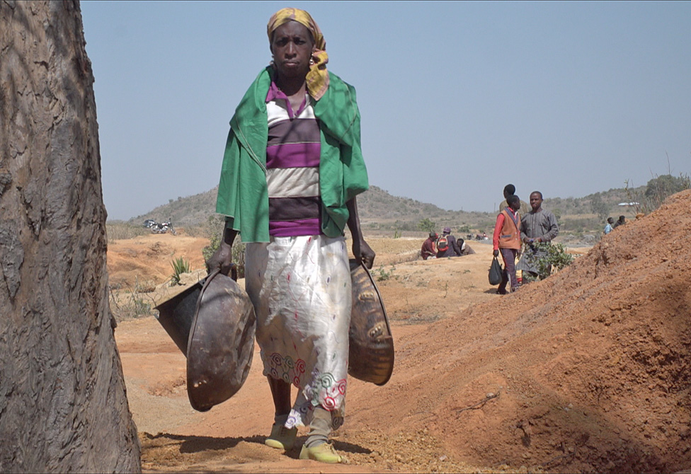 A woman carries metal pans at the Barkin Ladi mine