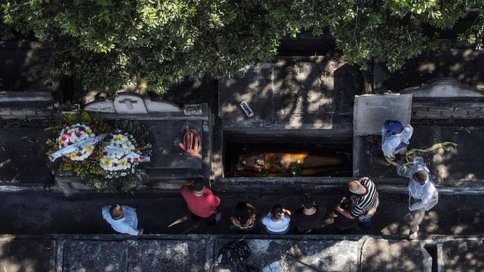 Foto aérea mostra caixão em vala, com pessoas em volta, prestando homenagem ao corpo