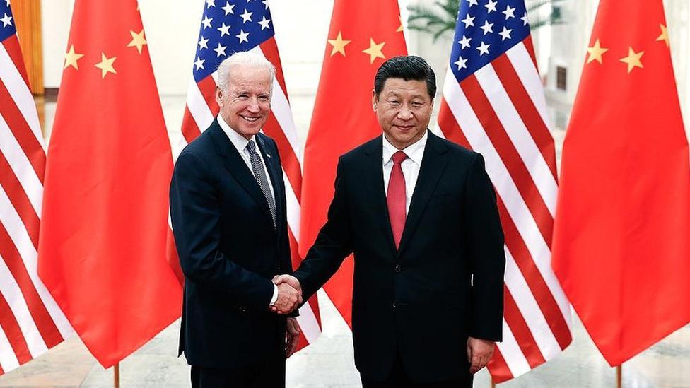 Joe Biden shakes hands with Chinese President Xi Jingping.