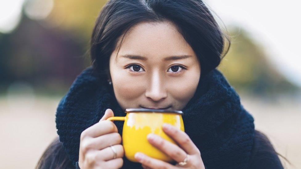 Una mujer toma una taza de té.