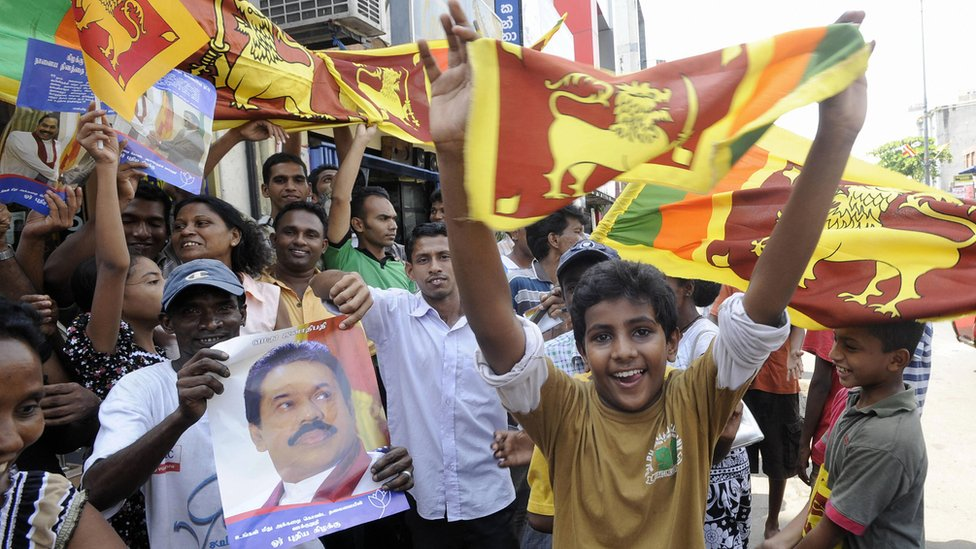 Jubilant crowds take to the streets of Colombo in May 2009 waving flags and holding pictures of Rajapaksa