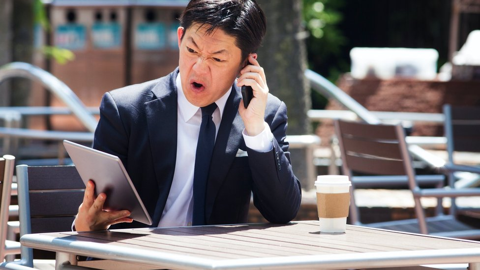 A man, on the phone, pulling faces which make you believe he's swearing angrily