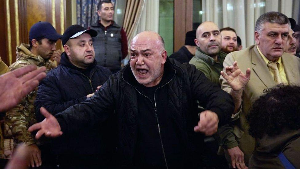 Un hombre grita enojado entre una multitud de manifestantes que asaltaron la oficina del primer ministro armenio, Nikol Pashinyan.