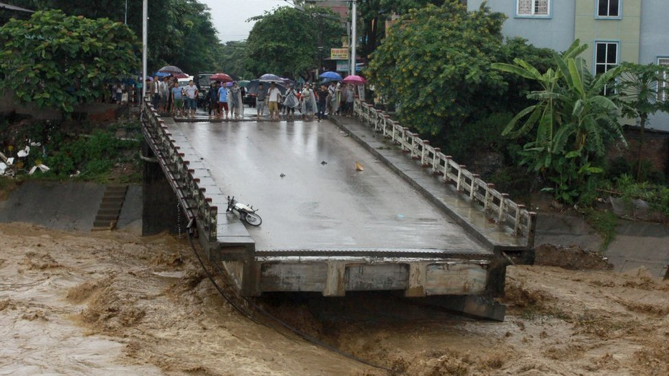 This picture from the Vietnam News Agency taken on 11 October 2017 shows residents standing at an end of a destroyed bridge in the northern province of Yen Bai.