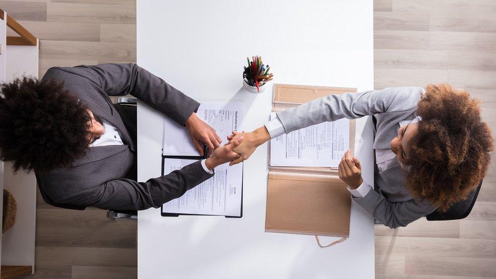 Vista elevada de dos personas dándose la mano.