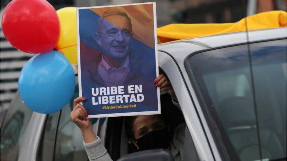 Un partidario de Álvaro Uribe, ex presidente y legislador de Colombia, usa una mascarilla y sostiene un cartel que dice