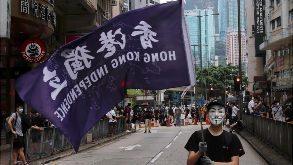 "A masked anti-government protester holds a flag supporting Hong Kong independence during a march against Beijing""s plans to impose national security legislation in Hong Kong, China May 24, 2020. REUTERS/Tyrone Siu"
