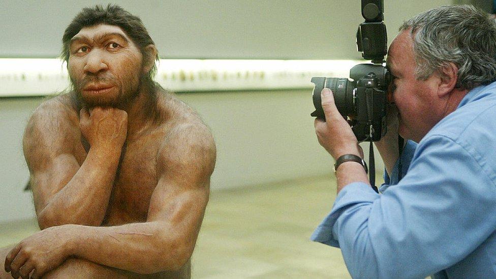 Hombre fotografiando una reproducción de un neandertal.