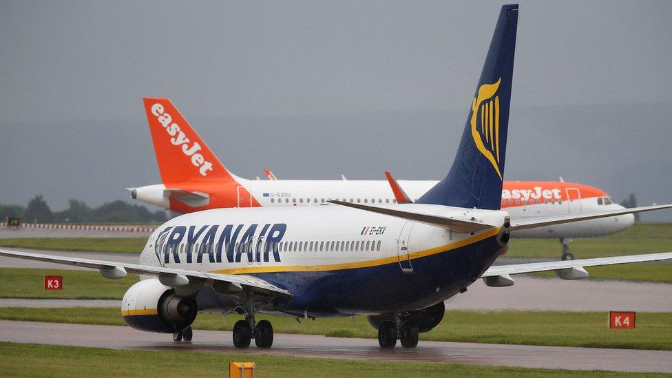A Ryanair aircraft taxis behind an easyJet aircraft at Manchester Airport