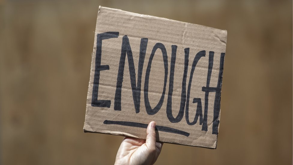 A person holds up a sign that reads 'Enough'