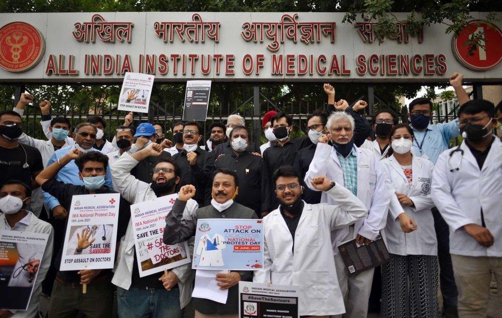 Médicos indianos de máscara e jaleco seguram cartazes e fazem protesto