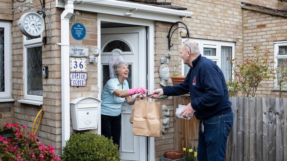 A volunteer delivering food
