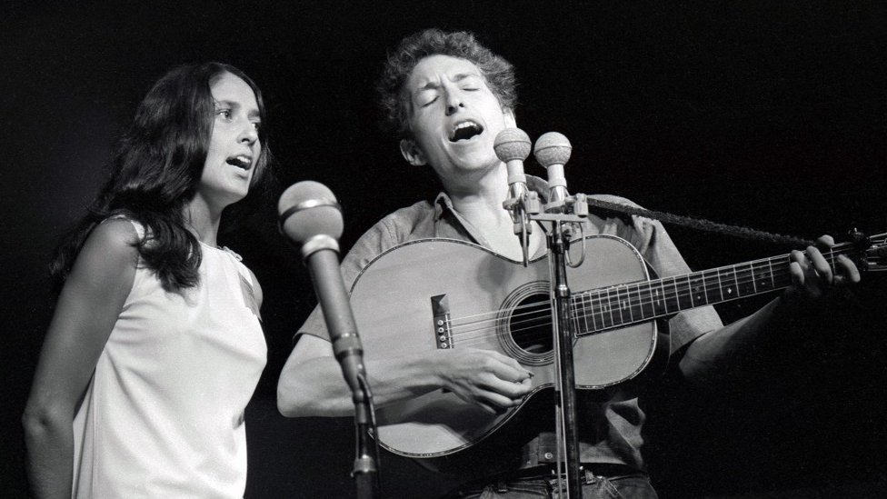 Joan Baez and Bob Dylan singing on stage