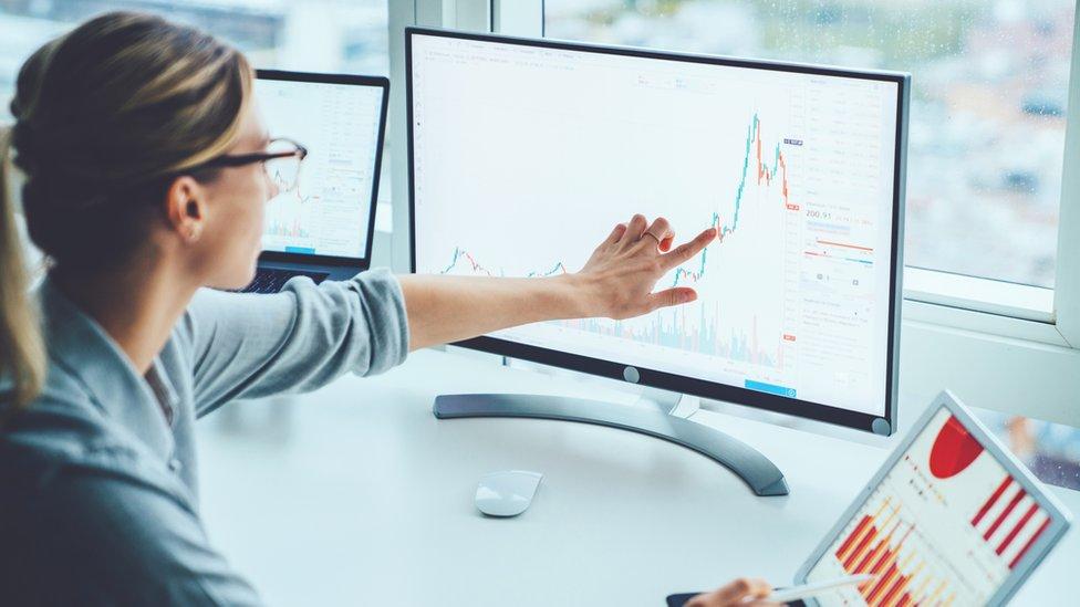 Mujer frente a computador en oficina
