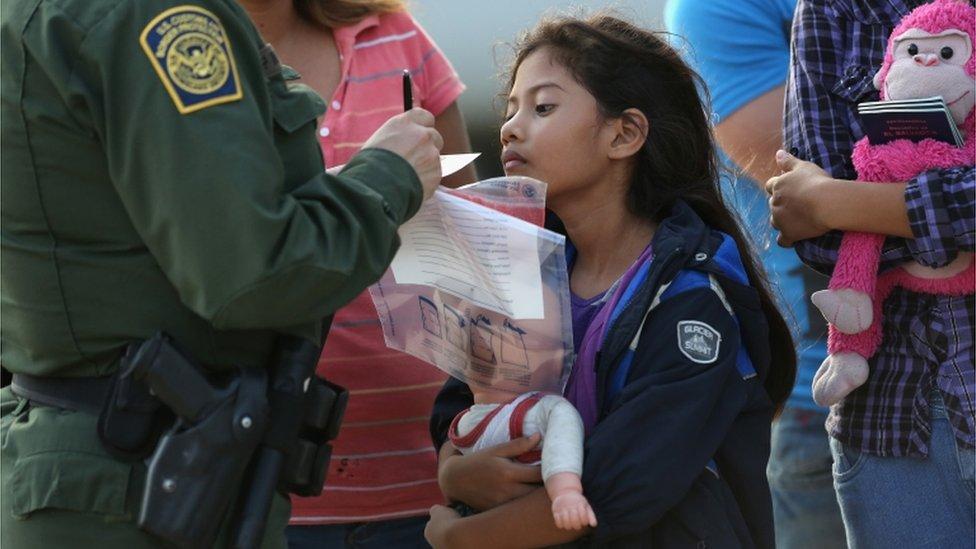 Una niña migrante presta atención a las instrucciones de un agente de la Patrulla Fronteriza de EE.UU.