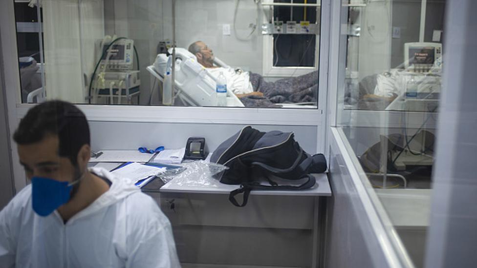 Profissional da saúde trabalha com paciente em maca ao fundo