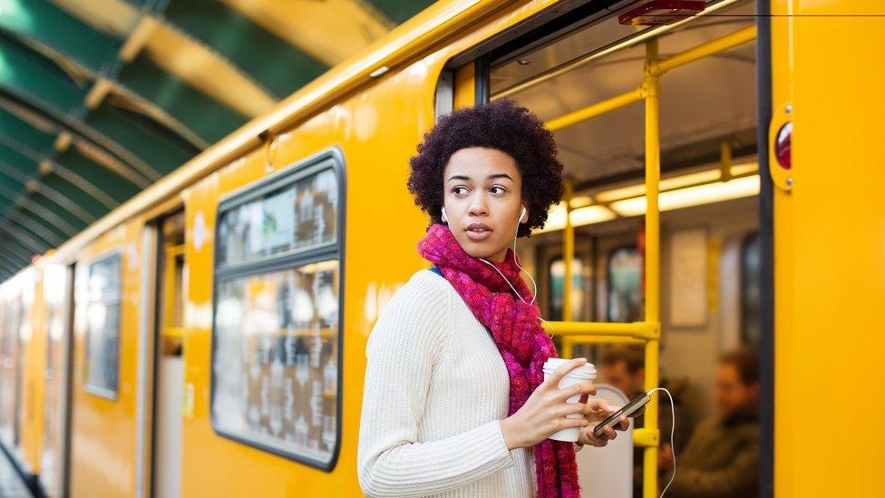 Mujer joven entrando en el metro y mirando hacia atrás.