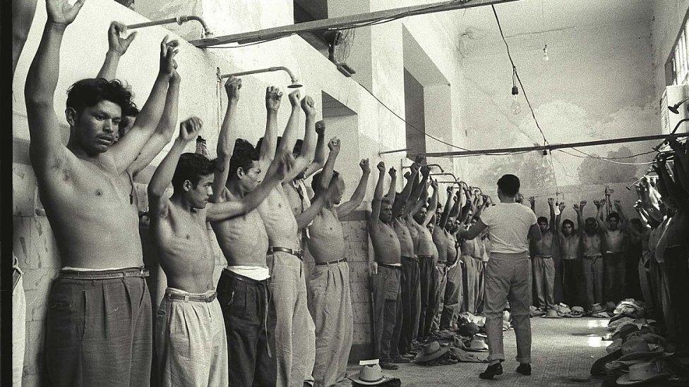 Un grupo de trabajadores del programa Bracero alzan los brazos y están alineados contra la pared mientras son inspeccionados en una habitación del Centro de Procesamiento en Monterrey, México.