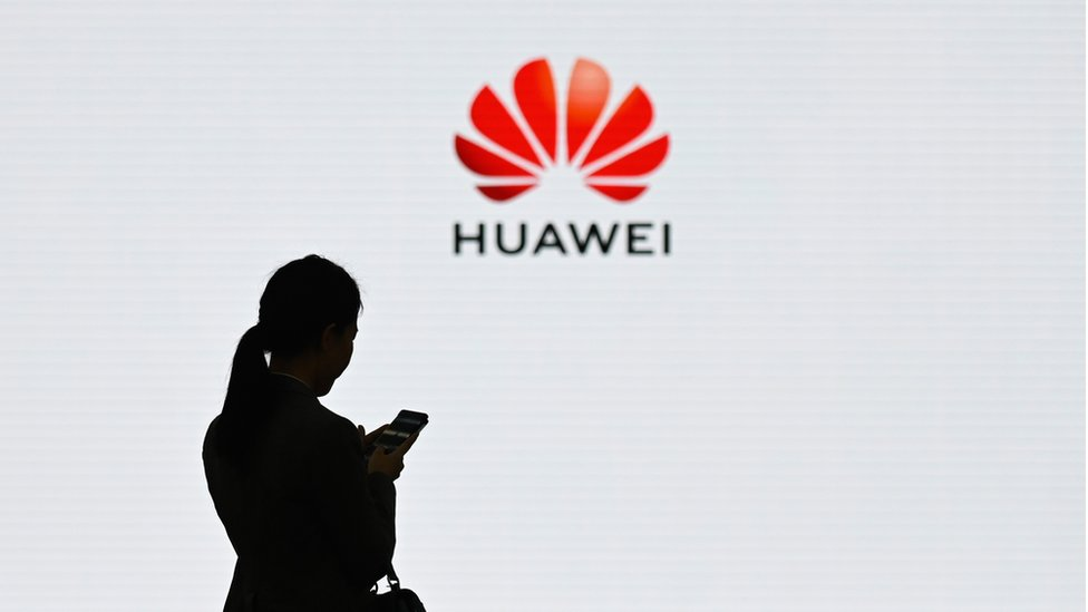 A staff member of Huawei uses her mobile phone