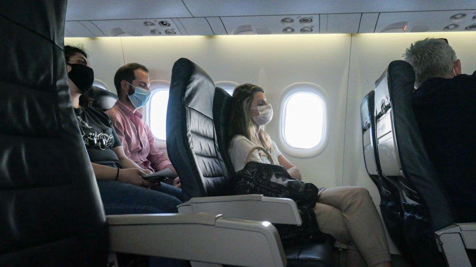 Pasajeros con mascarilla en un avión