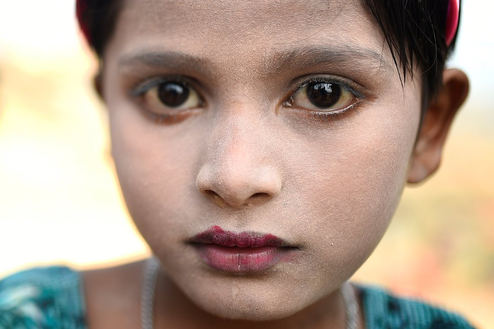 Rohingya refugee Sufaida, aged 7, poses for a photograph as she wears thanaka paste at Kutupalong camp in Cox's Bazaar, Bangladesh