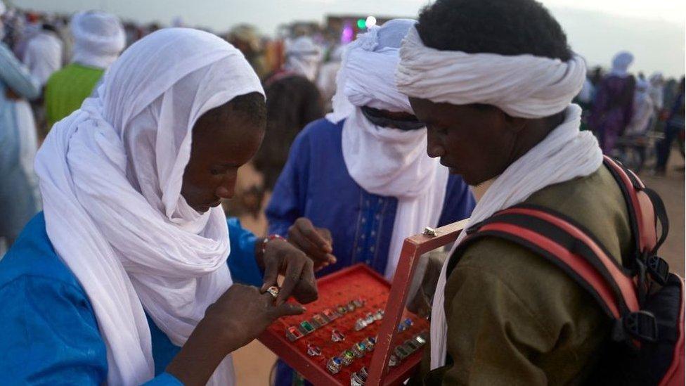 الرجال يقيسون الخواتم خلال المهرجان السنوي