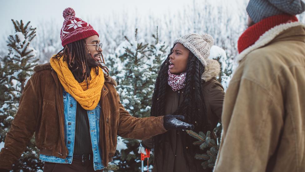 Un hombre y una mujer con ropas que hacen alusión a la Navidad discutiendo