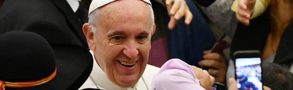 Pope Francis greets people during his weekly general audience at the Paul VI audience Hall on December 7,